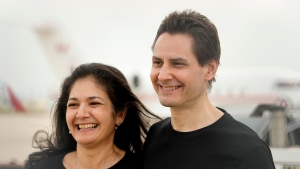 Michael Kovrig embraces his wife Vina Nadjibulla, left, after arriving at Pearson International Airport in Toronto, Saturday, Sept. 25, 2021. Two Canadians who were imprisoned in China for nearly three years are home. THE CANADIAN PRESS/Frank Gunn