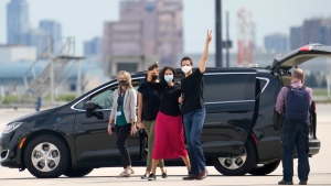 Michael Kovrig, centre right, and his wife Vina Nadjibulla, centre left, wave to media at Pearson International Airport in Toronto, Saturday, Sept. 25, 2021. Two Canadians who were imprisoned in China for nearly three years are home. THE CANADIAN PRESS/Frank Gunn