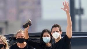 Michael Kovrig, centre right, waves to media as his wife Vina Nadjibulla, centre left, and sister Ariana Botha, left, after his arrival at Pearson International Airport in Toronto, Saturday, Sept. 25, 2021. Two Canadians who were imprisoned in China for nearly three years are home. THE CANADIAN PRESS/Frank Gunn
