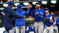 Toronto Blue Jays centerfielder George Springer, center, and other players go through the celebration line after the Blue Jays' 6-1 win over the Minnesota Twins in a baseball game, Saturday, Sept. 25, 2021, in Minneapolis. Springer hit a two-run home run in the game. (AP Photo/Jim Mone)