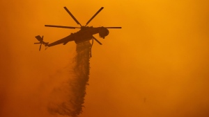 FILE - A helicopter drops water on the Fawn Fire burning north of Redding in Shasta County, Calif., on Thursday, Sept. 23, 2021. (AP Photo/Ethan Swope)
