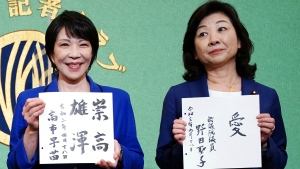 Sanae Takaichi, left, and Seiko Noda, right, both former internal affairs ministers and candidates for the presidential election of the ruling Liberal Democratic Party, show their motto on cards, during a debate session held by Japan National Press club Saturday, Sept. 18, 2021 in Tokyo. Takaichi and Noda are the first women in 13 years seeking the leadership of the ruling Liberal Democratic Party in an election Wednesday, Sept. 29. (AP Photo/Eugene Hoshiko, Pool)