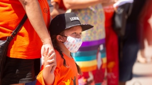 A young child listens to Chief Dennis Meeches talk during the Every Child Matters rally in front of the Canadian Museum for Human Rights in Winnipeg, Thursday, July 1, 2021. THE CANADIAN PRESS/Mike Sudoma