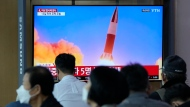 People watch a TV showing a file image of North Korea's missile launch during a news program at the Seoul Railway Station in Seoul, South Korea, Tuesday, Sept. 28, 2021. North Korea on Tuesday fired a suspected ballistic missile into the sea, Seoul and Tokyo officials said, the latest in a series of weapons tests by Pyongyang that raised questions about the sincerity of its recent offer for talks with South Korea. (AP Photo/Ahn Young-joon)
