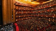 """In this photo provided by the Metropolitan Opera, the audience stands for the national anthem before the performance of Terence Blanchard's """"Fire Shut Up in My Bones,"""" which opened the Metropolitan Opera's 2021-2022 season on Monday, Sept. 27, 2021, in New York. (Jonathan Tichler/Metropolitan Opera via AP)"""