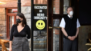 A sign encouraging vaccination is seen at the doors of a pub as staff watch patrons arrive, in Ottawa on the first day of Ontario's first phase of re-opening amidst the third wave of the COVID-19 pandemic, on Friday, June 11, 2021. THE CANADIAN PRESS/Justin Tang