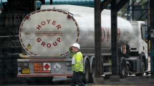 A worker walks by a fuel tanker at the Valero Manchester Terminal, in Manchester, England, Tuesday, Sept. 28, 2021. Thousands of British gas stations have run dry, as motorists scrambled to fill up amid a supply disruption due to a shortage of truck drivers. Long lines of vehicles formed at many gas stations over the weekend, and tempers frayed as some drivers waited for hours. (AP Photo/Jon Super)