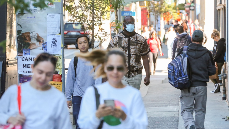 A man walking along Queen Street West wears a mask to help curb the spread of COVID-19 in Toronto on Tuesday, September 28, 2021. THE CANADIAN PRESS/Evan Buhler