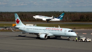A Westjet aircraft takes off as an Air Canada jet is towed on the tarmac at the Halifax airport on Tuesday, Sept. 20, 2011. A tentative agreement was reached Tuesday afternoon to avert a strike by Air Canada flight attendants. THE CANADIAN PRESS/Andrew Vaughan