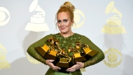 """FILE - Adele poses in the press room with the awards for album of the year for """"25,"""" song of the year for """"Hello,"""" record of the year for """"Hello,"""" best pop solo performance for """"Hello,"""" and best pop vocal album for """"25"""" at the 59th annual Grammy Awards on Feb. 12, 2017, in Los Angeles. (Photo by Chris Pizzello/Invision/AP, File)"""