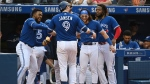 Toronto Blue Jays' Danny Jansen (9) celebrates with Teoscar Hernandez, left, Bo Bichette and Vladimir Guerrero Jr., right, after hitting a solo home run in the fifth inning of an American League baseball game against the Baltimore Orioles in Toronto on Saturday, Oct. 2, 2021. THE CANADIAN PRESS/Jon Blacker