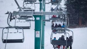 Skiers wait on the chair lift after a power failure shut down all operations at the women's World Cup downhill ski race at Lake Louise, Alta., Saturday, Dec. 2, 2017. THE CANADIAN PRESS/Jeff McIntosh
