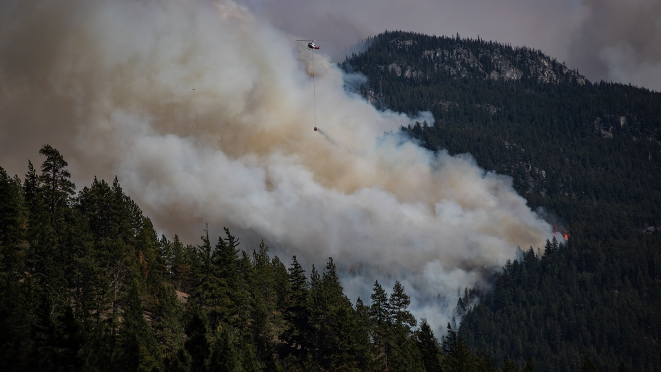 A helicopter carrying a water bucket flies past the Lytton Creek wildfire burning in the mountains near Lytton, B.C., on Sunday, August 15, 2021. THE CANADIAN PRESS/Darryl Dyck