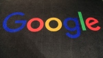 FILE - In this Nov. 18, 2019 file photo, the logo of Google is displayed on a carpet at the entrance hall of Google France in Paris. A new search feature rolled out Wednesday, Oct. 6, 2021 tells users which flights have lower carbon emissions, giving them the ability to choose flights based on carbon emissions just as they would price or the number of layovers. (AP Photo/Michel Euler, File)