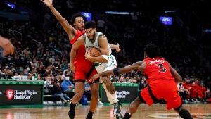 Boston Celtics' Jayson Tatum, center, goes between Toronto Raptors' OG Anunoby (3) and Scottie Barnes during the second quarter of an NBA preseason basketball game Saturday, Oct. 9, 2021, in Boston. (AP Photo/Winslow Townson)