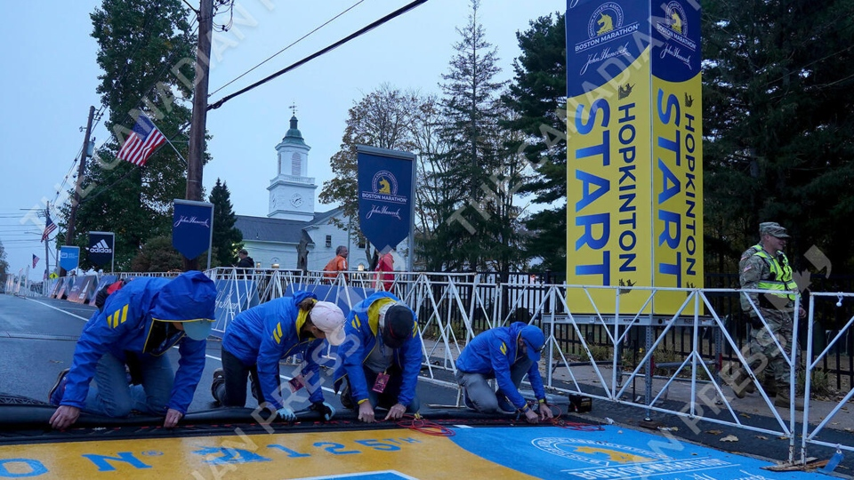 Volunteers put the finishing touches on the timing mat at the starting line of the 125th Boston Marathon, Monday, Oct. 11, 2021, in Hopkinton, Mass. (AP Photo/Mary Schwalm)