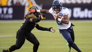Toronto Argonauts wide receiver Ricky Collins Jr. (2) blocks a tackle by Hamilton Tiger Cats defensive back Tunde Adeleke (2) during second half CFL football game action in Hamilton, Ont., Monday, Oct. 11, 2021. THE CANADIAN PRESS/Nick Iwanyshyn