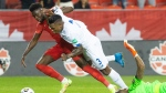 Canada's Alphonso Davies (left) goes down under Harold Cummings' challenge after rounding Panama goalkeeper Luis Mejia during first half World Cup qualifying action in Toronto, on Wednesday, October 13, 2021. THE CANADIAN PRESS/Chris Young