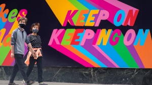 A couple walk past an inspirational mural in Toronto during the COVID-19 pandemic on Tuesday May 25, 2021. THE CANADIAN PRESS/Frank Gunn