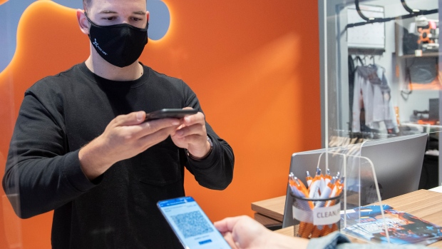 Jonathan Gagne, manager of Orangetheory Fitness, scans the COVID-19 QR code of a client in Montreal, Wednesday, September 1, 2021, as the Quebec government's COVID-19 vaccine passport comes into effect. THE CANADIAN PRESS/Graham Hughes