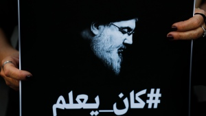 """A Lebanese protester holds a portrait of Hezbollah leader Sayyed Hassan Nasrallah with Arabic that reads: """"He knew"""" (about the thousand tons of ammonium nitrates that exploded last year at Beirut seaport), during a protest against the Hezbollah group and the visit of the Iranian foreign minister Hossein Amirabdollahian  Thursday, in Beirut, Lebanon, Wednesday, Oct. 6, 2021. (AP Photo/Hussein Malla)"""