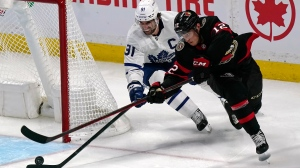 Ottawa Senators' Shane Pinto (12) tries a wrap-around as Toronto Maple Leafs' John Tavares (91) defends during second period NHL hockey action in Ottawa on Thursday, October 14, 2021. THE CANADIAN PRESS/Adrian Wyld