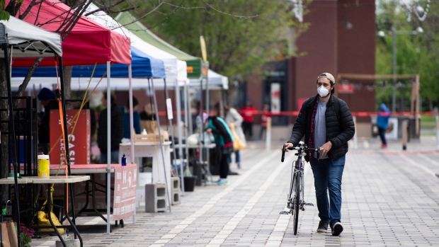 A customer is alone as they walk their bike to pick up an order at the Ottawa Farmers' Market at Lansdowne Park, which opened for online order pickups only due to the COVID-19 pandemic, in Ottawa, on Sunday, May 31, 2020. THE CANADIAN PRESS/Justin Tang
