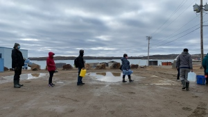 Residents line up to fill containers with potable water in Iqaluit, Nunavut on Thursday, Oct. 14, 2021. The Nunavut government has declared a 14-day state of emergency in Iqaluit after water in the capital was deemed undrinkable and potentially tainted with petroleum. The first shipment of potable water for residents also arrived by plane, with more expected to be delivered in the coming days.THE CANADIAN PRESS/Emma Tranter