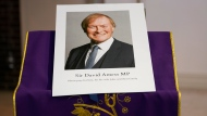 An image of murdered British Conservative lawmaker David Amess is displayed near the altar in St Peters Catholic Church before a vigil in Leigh-on-Sea, Essex, England, Friday, Oct. 15, 2021. Amess died after being stabbed earlier Friday during a meeting with constituents at another nearby church in eastern England. Police gave no immediate details on the motive for the killing of 69-year-old Conservative lawmaker Amess and did not identify the suspect, who was being held on suspicion of murder. (AP Photo/Alberto Pezzali)