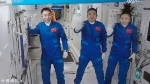 """In this photo released by Xinhua News Agency, screen image captured at Beijing Aerospace Control Center in Beijing, China, Saturday, Oct. 16, 2021 shows three Chinese astronauts, from left, Ye Guangfu, Zhai Zhigang and Wang Yaping waving after entering the space station core module Tianhe. China's Shenzhou-13 spacecraft carrying three Chinese astronauts on Saturday docked at its space station, kicking off a record-setting six-month stay as the country moves toward completing the new orbiting outpost. Chinese characters, left, read """"Platform Camera B."""" (Tian Dingyu/Xinhua via AP)"""