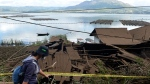 A woman walks past houses by Lake Batur which were damaged by an earthquake-triggered landslide in Bangli, on the island of Bali, Indonesia, Saturday, Oct. 16, 2021. A few people were killed and another several were injured when a moderately strong earthquake and an aftershock hit the island early Saturday. (AP Photo/Dewa Raka)