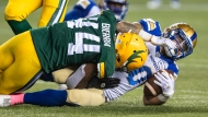 Winnipeg Blue Bombers' Brady Oliveira (20) is tackled by Edmonton Elks' Keishawn Bierria (44) during second half CFL action in Edmonton, on Friday, October 15, 2021. THE CANADIAN PRESS/Jason Franson