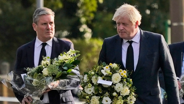 British Prime Minister Boris Johnson, right, and Leader of the Labour Party Keir Starmer carry flowers as they arrive at the scene where a member of Parliament was stabbed Friday, in Leigh-on-Sea, Essex, England, Saturday, Oct. 16, 2021. David Amess, a long-serving member of Parliament was stabbed to death during a meeting with constituents at a church in Leigh-on-Sea on Friday, in what police said was a terrorist incident. A 25-year-old man was arrested in connection with the attack, which united Britain's fractious politicians in shock and sorrow. (AP Photo/Alberto Pezzali)