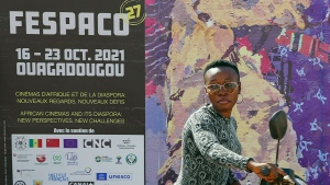A woman pushes her scooter past the entrance of FESPACO (Pan-African Film & TV Festival of Ouagadougou) in Ouagadougou, Burkina Faso, Friday Oct. 15, 2021. The event, now in its 52nd year, is attracting filmmakers and moviegoers from across the continent and the globe. (AP Photo/Sam Mednick)
