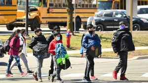 Students cross the street at Tomken Road Middle School as Ontario prepares for its third province wide lockdown during the COVID-19 pandemic in Mississauga, Ont., on Thursday, April 1, 2021. Schools will remain open during the four week emergency brake lockdown. THE CANADIAN PRESS/Nathan Denette