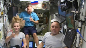 In this photo taken from video footage released by Roscosmos Space Agency, actress Yulia Peresild, left, film director Klim Shipenko, center, and cosmonaut Anton Shkaplerov speak with the Moscow Mission Control Center from the International Space Station, ISS, Thursday, Oct. 7, 2021. Actress Yulia Peresild and film director Klim Shipenko blasted off Tuesday for the International Space Station in a Russian Soyuz spacecraft together with cosmonaut Anton Shkaplerov, a veteran of three space missions, to make a feature film in orbit. (Roscosmos Space Agency via AP)