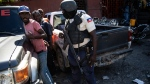 A policeman detains a commuter at a checkpoint in downtown Port-au-Prince, Haiti, Thursday, Sept. 30, 2021. (AP Photo/Rodrigo Abd)