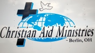 This Sunday, Oct. 17, 2021 photo shows the logo for Christian Aid Ministries in Berlin, Ohio, on a truck. A group of 17 missionaries including children has been kidnapped by a gang in Haiti, according to a voice message sent to various religious missions by the organization. The message from Ohio-based Christian Aid Ministries said the missionaries were on their way home from building an orphanage. (AP Photo/Tom E. Puskar)