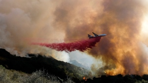 FILE - In this Oct. 13, 2021, file photo, an air tanker drops retardant on a wildfire in Goleta, Calif. Firefighters persisted in making progress Saturday, Oct. 17, against a wildfire burning for a sixth day in Southern California coastal mountains. The Alisal Fire in the Santa Ynez Mountains west of Santa Barbara grew only slightly since Friday to nearly 27 square miles (69 square kilometers). It was 50% contained. (AP Photo/Ringo H.W. Chiu, File)