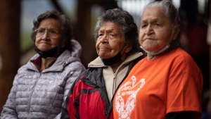 Kamloops Indian Residential School survivors and sisters, from left to right, Doreen Kenoras, 74, Sadie Kenoras, 79, and Camille Kenoras, 82, listen during a Tk'emlups te Secwepemc ceremony to honour residential school survivors and mark the first National Day for Truth and Reconciliation, in Kamloops, BC., on Thursday, September 30, 2021. The remains of 215 children were discovered buried near the former Kamloops Indian Residential School earlier this year. THE CANADIAN PRESS/Darryl Dyck