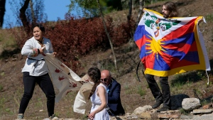 """A police officer tries to stop protesters displaying a Tibetan flag and a banner reading """"No genocide games"""" during the lighting of the Olympic flame at Ancient Olympia site, birthplace of the ancient Olympics in southwestern Greece, Monday, Oct. 18, 2021. The flame will be transported by torch relay to Beijing, China, which will host the Feb. 4-20, 2022 Winter Olympics. (AP Photo/Thanassis Stavrakis)"""