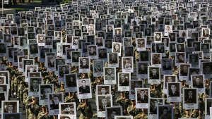 Azerbaijan's Army soldiers carry portraits of the soldiers killed during the fighting over Nagorno-Karabakh in 2020 year, during a memorial event in Baku, Azerbaijan, Monday, Sept. 27, 2021.  (AP Photo/Aziz Karimov)