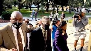 Ahmaud Arbery's father Marcus Arbery, center, heads into the Glynn County Courthouse in Brunswick, Ga with his attorney Benjamin Crump on Monday, Oct. 18, 2021. Jury selection got underway with hundreds of people ordered to report for what could be a long, laborious effort to find jurors to hear the trial of three white men charged with fatally shooting Ahmaud Arbery as he was running in their neighborhood. (AP Photo/Lewis M. Levine)