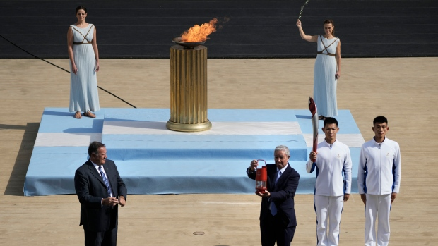 President of the Hellenic Olympic Committee Spyros Kapralos, left, looks on as Vice President of the Chinese Olympic Committee Mr.Yu Zaiqing, center, holds the Olympic flame during the Olympic flame handover ceremony at Panathinean stadium in Athens, Greece, Tuesday, Oct. 19, 2021. The flame will be transported by torch relay to Beijing, China, which will host the Feb. 4-20, 2022 Winter Olympics. (AP Photo/Petros Giannakouris)