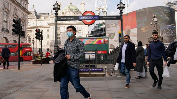 A man wears a face mask as he walks in Piccadilly Circus, in London, Tuesday, Oct. 19, 2021. Many scientists are pressing the British government to re-impose social restrictions and speed up booster vaccinations as coronavirus infection rates, already Europe's highest, rise once more. The U.K. recorded 49,156 new COVID-19 cases on Monday, Oct. 18, the largest number since mid-July. New infections averaged 43,000 a day over the past week, a 15% increase on the week before.(AP Photo/Alberto Pezzali)