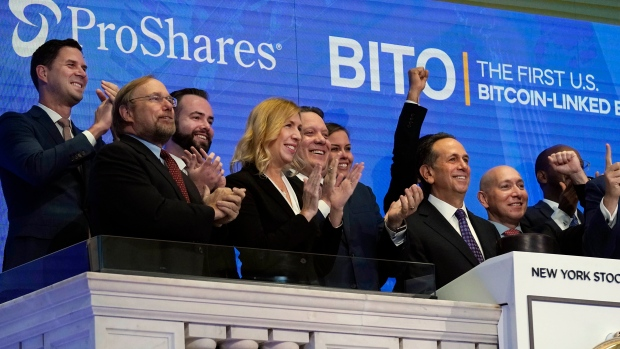 ProShares CEO Michael Sapir, second right, and company Global Investment Strategist Simeon Hyman, right, lead the New York Stock Exchange opening bell celebration, Tuesday, Oct. 19, 2021. ProShares will launch the country's first exchange-traded fund linked to Bitcoin. (AP Photo/Richard Drew)