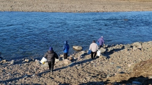 Qajuqturvik Community Food Centre staff members fill water jugs at the Sylvia Grinnell River, just outside Iqaluit, in an undated handout photo. The group has been delivering water to homes and organizations that may not have their own transportation, after the city warned last week its tap water was contaminated with fuel. THE CANADIAN PRESS/HO-Rachel Blais.