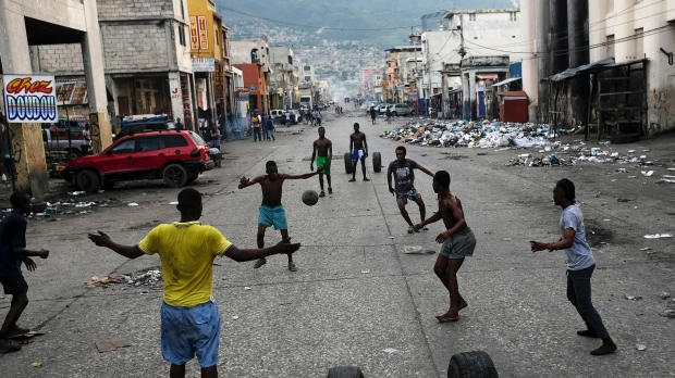 Youths play soccer next to businesses that are closed due to a general strike in Port-au-Prince, Haiti, Monday, Oct. 18, 2021. Workers angry about the nation's lack of security went on strike in protest two days after 17 members of a US-based missionary group were abducted by a violent gang. (AP Photo/Matias Delacroix)