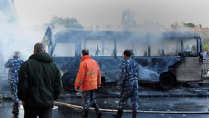 In this photo released by the Syrian official news agency SANA, Syrian firefighters and security officer check a burned bus at the site of a deadly explosion, in Damascus, Syria, Wednesday, Oct. 20, 2021. Two roadside bombs exploded near a bus carrying troops during the morning rush hour in the Syrian capital early Wednesday, killing and wounding several people, state TV reported. (SANA via AP)