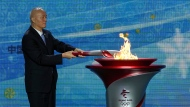 Cai Qi, Beijing Communist Party secretary lits up the Olympic cauldron during a welcome ceremony for the Flame of Olympic Winter Games Beijing 2022, held at the Olympic Tower in Beijing, Wednesday, Oct. 20, 2021. A welcome ceremony for the Olympic flame was held in Beijing on Wednesday morning after it arrived at the Chinese capital from Greece. While the flame will be put on display over the next few months, organizers said a three-day torch relay is scheduled starting February 2nd with around 1200 torchbearers in Beijing, Yanqing and Zhangjiakou. (AP Photo/Andy Wong)